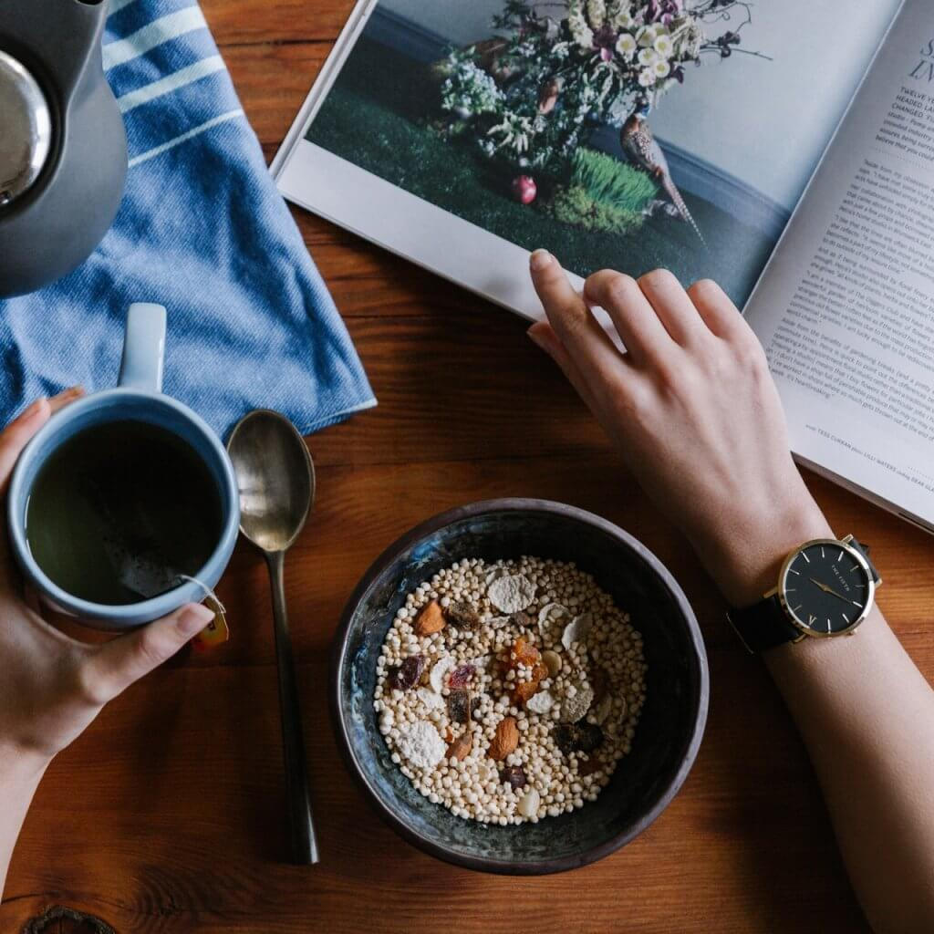View from above of table with person with coffee, cereal, and a magazine