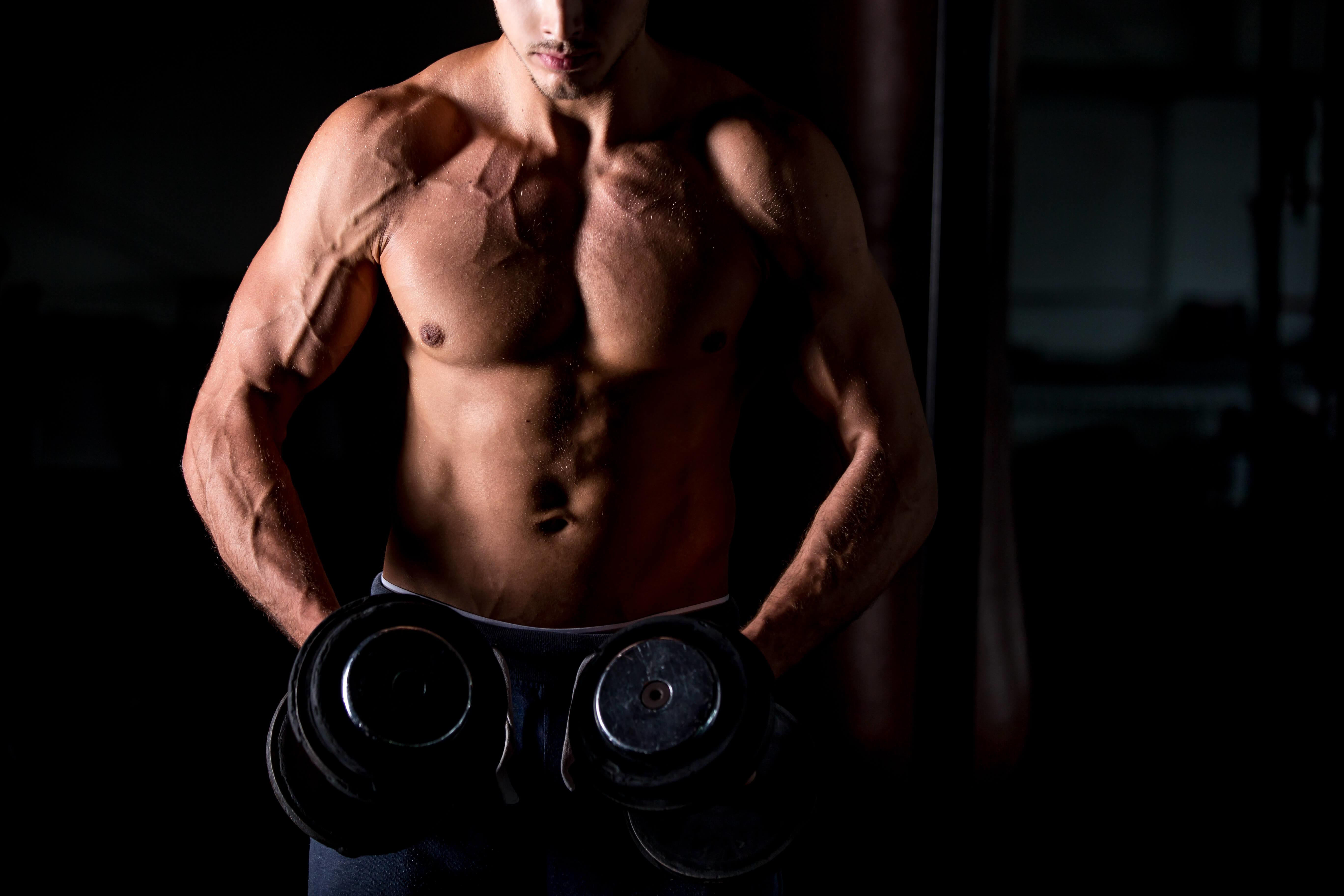 Young attractive caucasian bodybuilder sportsman working out with dumbbells in gym, doing training for shoulder muscles, close up