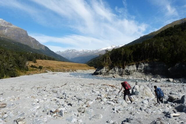 A hiker crossing a riverbed alluvial fan. Rees Dart Track, New Zealand