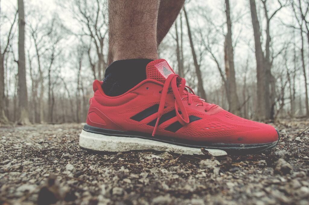 shot of a man's red running shoe in the forest
