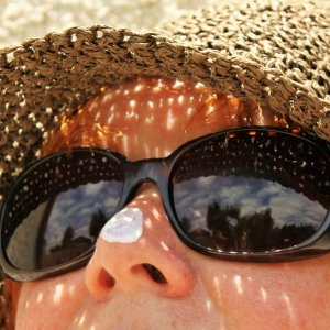 a women with sunscreen on her nose, wearing a hat and sunglasses