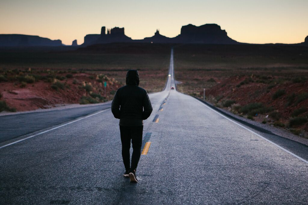 a solitary figure walking alone down a deserted highway in the desert