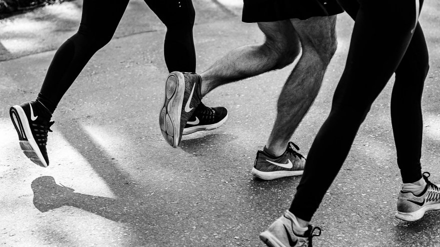 different runners' feet as they run on pavement