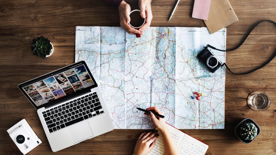 laptop, map, planning route over coffee