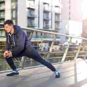 male runner lunging on bridge