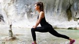 a woman doing a lunge stretch outdoors